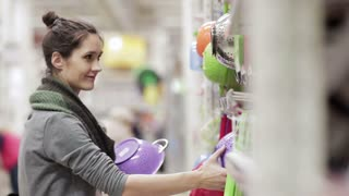 Young woman chooses dishes in the supermarket
