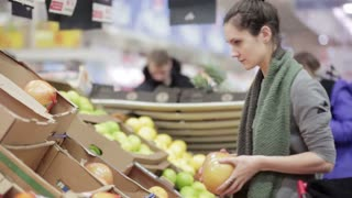 Young woman chooses ripe pomelo on store shelves.