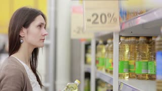 Young woman chooses sunflower oil in the store