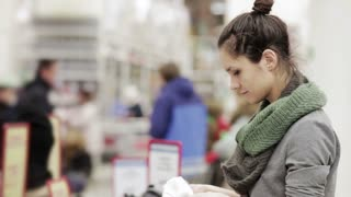 Young woman chooses winter hat in the supermarket