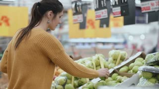 Young woman choosing a green apples in the supermarket, holding one fruit and then put into the package. 4K