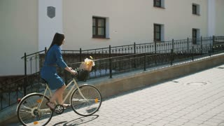 Young woman in a dress exploring the town on a bike with flowers in a basket in summertime, slow mom steadicam shot