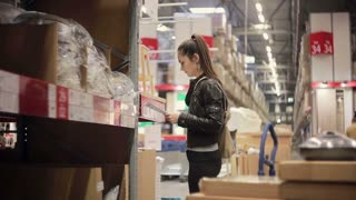Young woman is checking her list, taking a sink and pipes from a shelf and putting them on the trolley in a warehouse