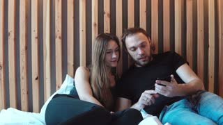 Young woman kisses man to the cheek, loving couple sitting on the bed. Male use the smartphone, shows photos to female.