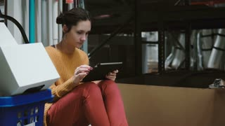 Young woman sitting at the warehouse and using tablet for checking goods list. 4K