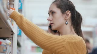 Young woman standing in front of supermarket shelves, holding phone and talking. Takes the item and asking advice. 4K