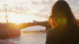 Young woman standing on the embankment makes on smartphone photo of the bridge in the bright rays of the setting sun. 4K