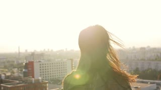 young woman standing on the roof at sunset turns the head and her hair looking at the camera. slow mo