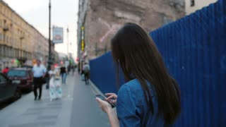 Young woman stands near a blue fence in the street. Lady uses a smartphone, turns her head to the camera. Slow mo