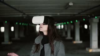 Young woman using a virtual reality glasses on parking place. Girl touching space with hand wearing VR headset. 4K