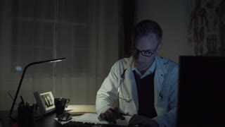 A man works at a clean desk with a computer and keyboard and mouse. He might have glasses on with a clock or medical chart in the background. The office has a window with late night or early morning light outside.