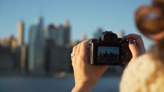 A woman takes pictures of NYC skyline. LD