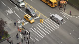 Aerial view of people walking across crosswalk of intersection