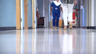 Nurse walks by an administrator
