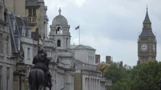 Buses pass by statue of George IV and Big Ben