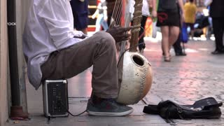 View of black street musician playing a kora
