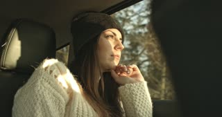 Young woman looking through a car window