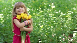 3s girl hugging a bouquet of yellow tulips