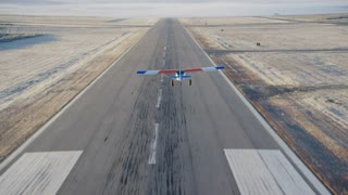 4K Aerial air to air of plane flying over runway