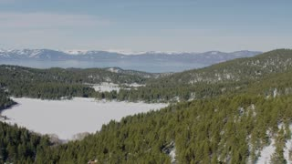 4K Aerial flying over snowy Lake Tahoe forest