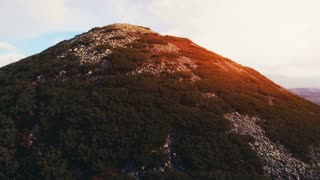 4K Aerial Drone Footage: Flight above mountain peak in dramatic red sunset light. Hills and cloudy sky in the background. Carpathian Mountains, Ukraine, Europe. Majestic nature landscape. Beauty world