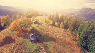 4K Aerial Drone View: Low Flight over sunny autumn mountains with old farm houses in sunset soft light. Carpathian Mountains, Ukraine, Europe. Majestic nature landscape. Beauty world. Vintage toning