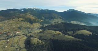 4K Aerial Flight above beautiful village on green slopes of Carpathian mountains. Beautiful world. Bukovel, Ukraine