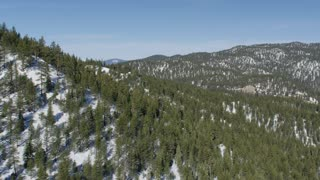 4K Aerial Flying Over Snowy Hills and Forest