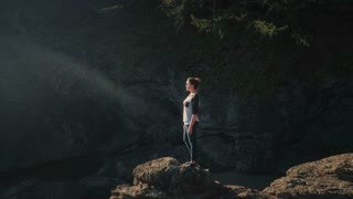 4K Aerial pull away shot of Woman Standing on Ocean Cliff