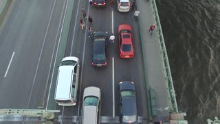 4k Aerial shot of a crowd of young people walk on the bridge between staying cars