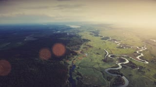 4K Aerial View Drone Footage Flight: 180 degree high shooting of Beautiful River and Green Meadows in dramatic sunset light with sun beams. Turn right. Ukraine, Europe. Beauty world. Nature landscape