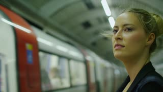 4K Attractive businesswoman watches a train go past at a subway station in slow motion, shot on RED EPIC