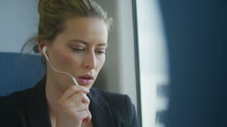 4K Attractive busy businesswoman on a train talking on her handsfree earpiece whilst working, shot on RED EPIC