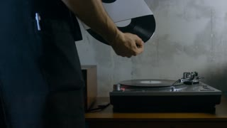 4K cinemagraph - motion photo seamless loop - young adult Caucasian male playing vinyl record on a vintage record player. Shot with Blackmagic URSA Mini