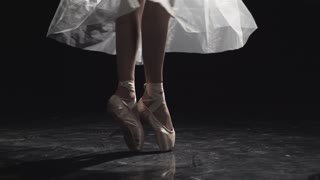 4k Close-up of the feet of a ballerina dancing on a wooden floor