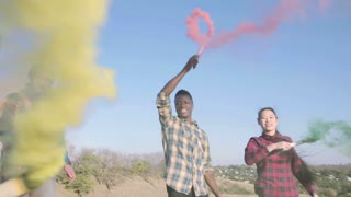 4K Four happy young multi racial friends dancing in field with colored smoke grenades