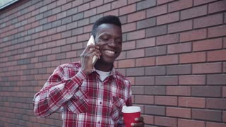 4K Joyful young African guy walking down the street along brickwall and talking on his cell phone with cup of coffee in city