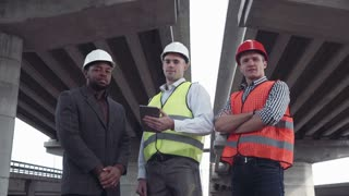 4K movement stabilized shot of front view of three architects one african and two caucasians in protective helmets looking at camera. Low angle wide shot