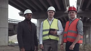 4K movement stabilized shot of front view of three architects one african and two caucasians in protective helmets looking at camera