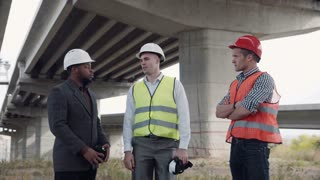 4K shot of business team of two architects and afro american foreman in suit uses virtual reality glasses to discuss a project of development while standing under overpass construction
