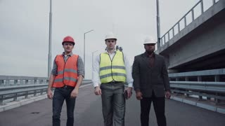 4K shot of Diverse group of three handsome male construction engineers with serious expressions walking on highway ramp