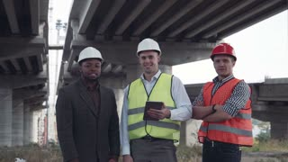 4K shot of front view of three architects one african and two caucasians in protective helmets hard hats looking at camera