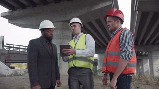 4K shot of structural engineers showing something on tablet to their bearded boss in white hard hat under newly constructed highway bridge