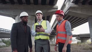 4K shot of three multiracial young male architects having a discussion on site about a building design standing in a row facing the camera, three-quarter closeup view