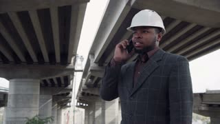 4K stabilized movement shot of smiling professional man in blank white hard hat on phone while standing under highway bridges