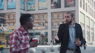 4K Two different people caucasian and afro american having a conversation till coffee break. Urban background