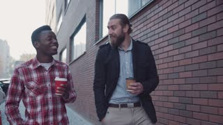 4K Two men walking along the big brick wall, having a conversation and sharing moments with smartphone's help while holding disposable coffee cups