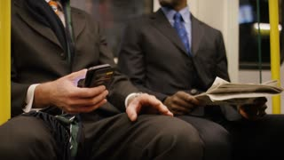 4K Two smart business men on a train commuting discuss investments in a newspaper