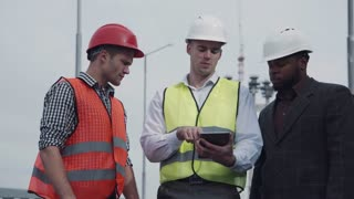 4K Workers in vests showing boss something on tablet computer while standing outside with tall street lamps behind them and demonstrating with hands