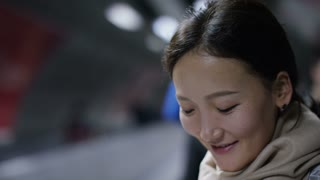 4K Young asian woman using her phone on a moving sidewalk, in slow motion